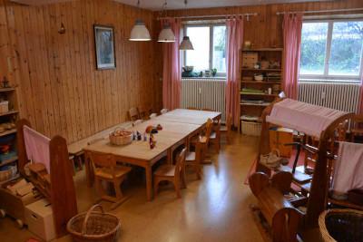 spielgruppen raum mit tisch, stühlen und der spielecke.