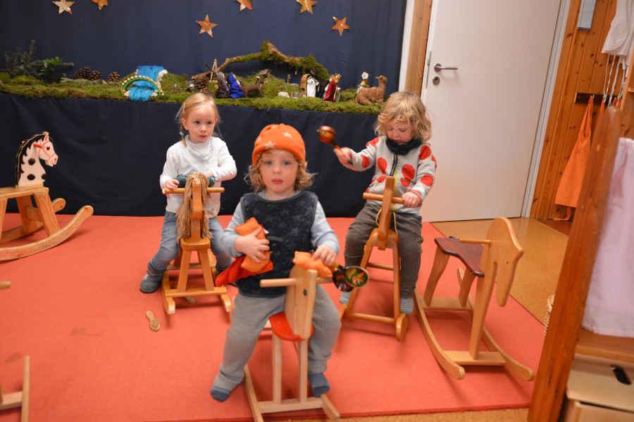 drei kinder reiten auf holzpferdchen durch die spielgruppen räume.