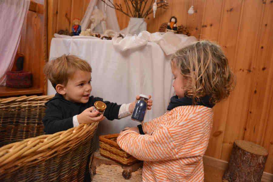 ein kleiner junge übergibt lachend einen gegenstand an ein anderes Kind