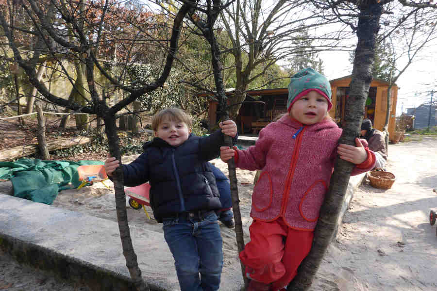 zwei kinder stehen in einer astgabel.