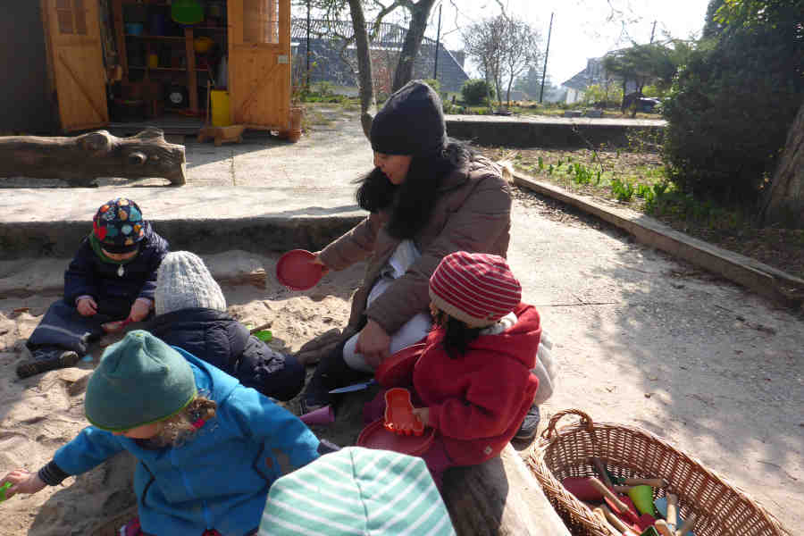 spielende kinder im sandkasten des spielgruppen gartens.