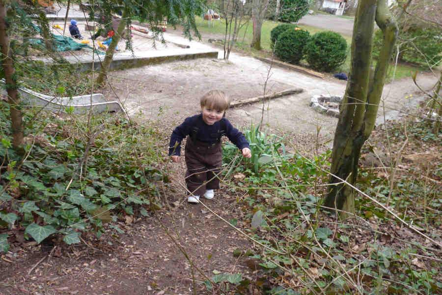 im spielgruppen garten läuft ein kleiner junge laechelnd einen berg hoch.
