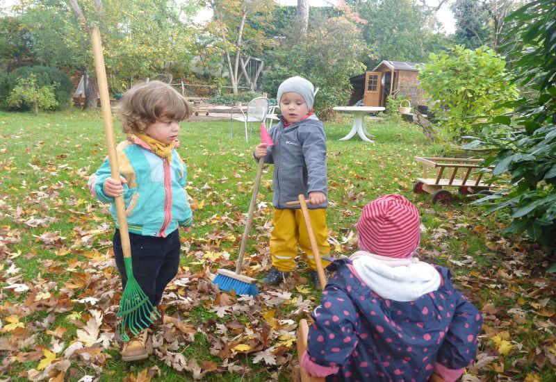 drei kinder spielen im garten