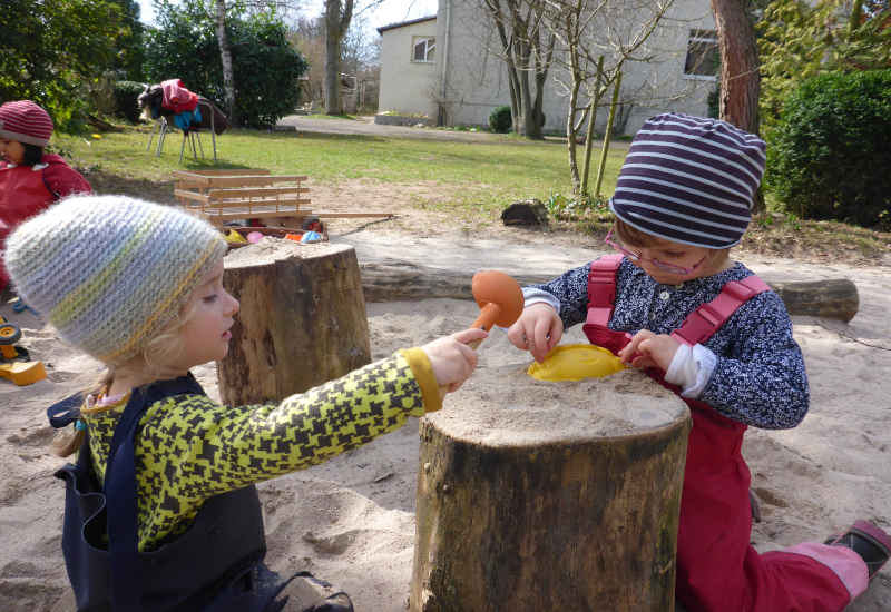 zwei kinder spielen im sandkasten der spielgruppe auf einem holzklotz