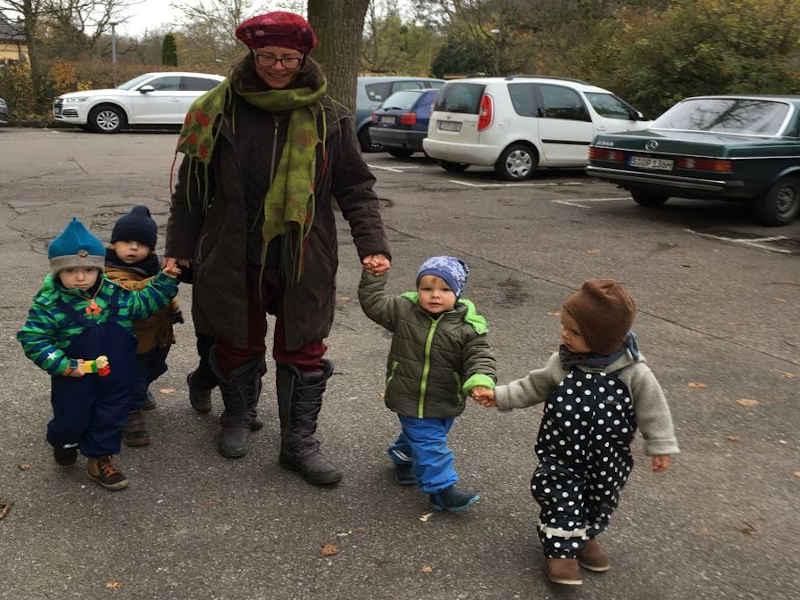 die spielgruppenleiterinn mit vier kindern an der hand