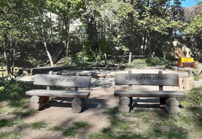 zwei kleine kinder sitzbänke mit der aufschrift spielgruppe rumpelstilzchen