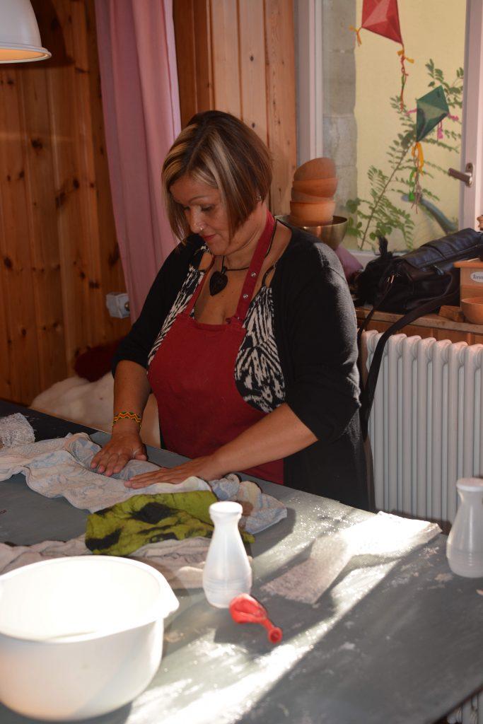 Frau die am Tisch steht und filzt