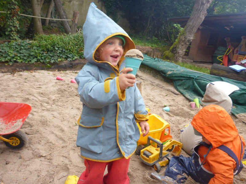 ein kind im sandkasten der spielgruppe mit einem sand eis in der hand