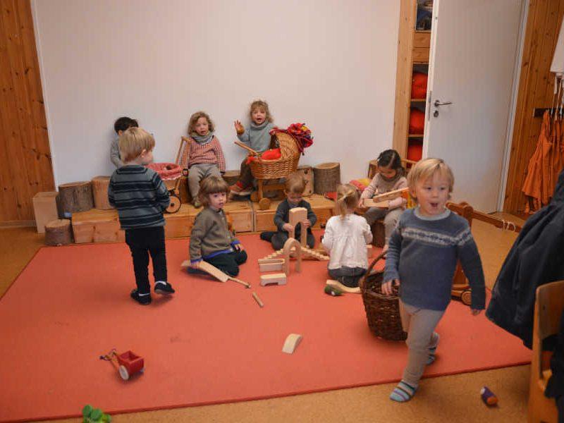 kinder in der spielgruppe auf einem roten teppich