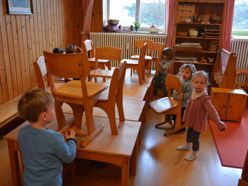 Kinder räumen stühle auf in der spielgruppe rumpelstilzchen